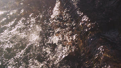 Slow motion shot of water flowing over rocks Footage