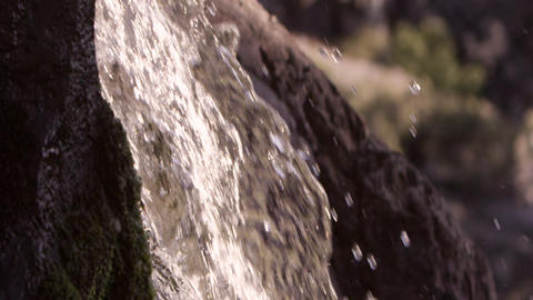 Slow motion closeup of white water splashing over rocks Footage
