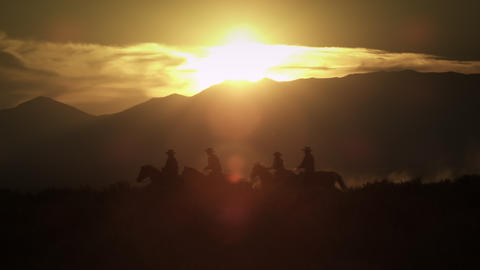Silhouetted cowboys riding at sunset, kicking up dust. Shot in slow motion with  Footage