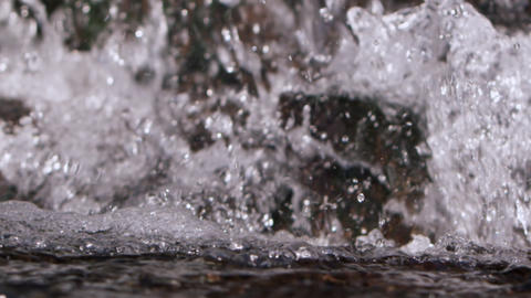 Slow motion closeup of water crashing at the bottom of a waterfall Footage