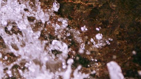 Close up rushing water splashing over rocks. Slow motion Footage