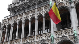 Belgian flag on the building of brussels city hall in grand place Footage