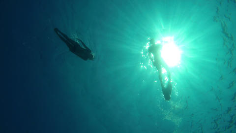 Couple swimmers shot from the bottom of the sea Footage