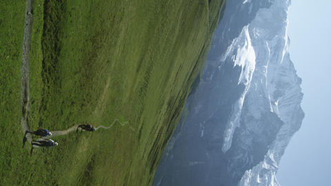 Static shot of hikers walking path at base of Swiss Alps Footage