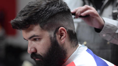 Handsome bearded man getting haircut by hairdresser at the barber shop Archivo