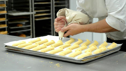 Professional Pastry chef preparing eclairs extruding the dough from a pastry bag Live Action