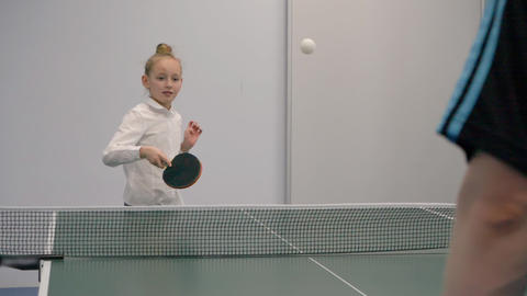 Young girl playing ping pong slow motion. Sport girl teenager playing ping pong Live Action