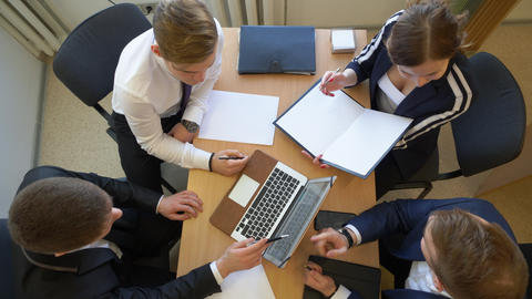 Overhead View Of Businesspeople Hands On Office Desk Using Electronic Devices Footage