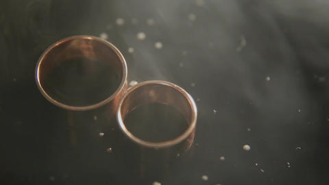 Thick smoke blowing into two wedding RING on wet black background. Close up Live Action