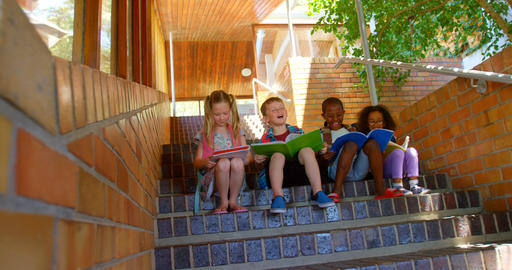 School children reading book while sitting on stairs of elementary school 4k Live Action