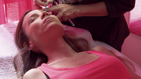 Young woman havind professional eyebrow correction at spa salon Live Action