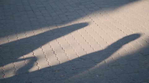 Evening shadow of a young couple in love on the pavement. Silhouette of two Live Action