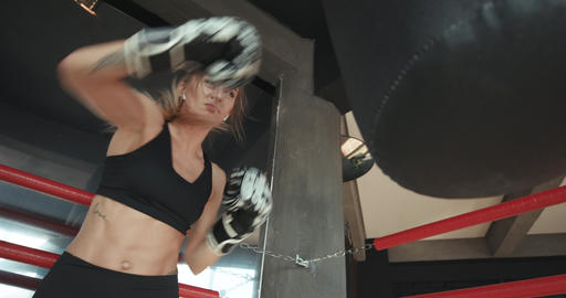 Athletic woman kickboxing, training with punching bag in the gym, slow motion Live Action