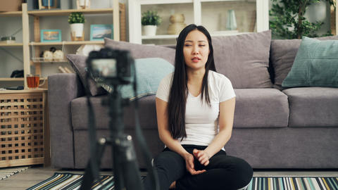 Cute Asian girl female blogger is recording video for her internet vlog looking Live Action