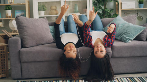 Carefree young women are listening to music through earphones using smartphone Live Action