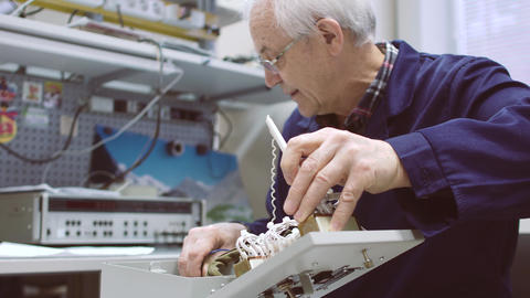 Elderly man working with electrical appliances. Tests the assembled circuit Live Action