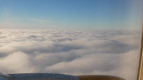 Plane flies above the clouds and going down enters the clouds Live Action