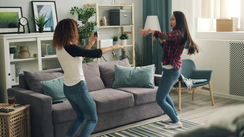 Cheerful young women are dancing at home relaxing and listening to music while Footage