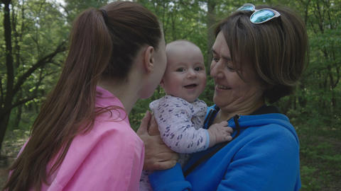 Happy family in the forest - mother kisses her baby and happy grandmother Live Action