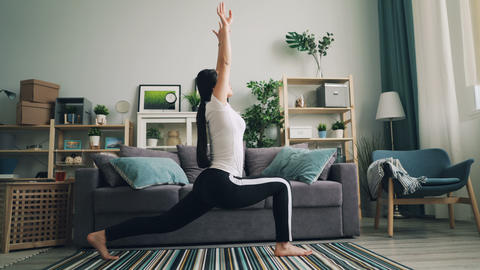 Flexible Asian girl is doing stretching exercises at home practising yoga poses Live Action