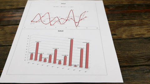 Slider shot. Sheet with red charts lying on an old wooden table, with copy space Footage
