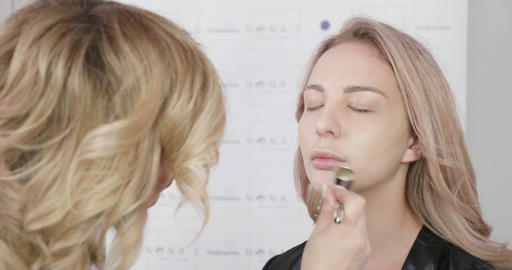 Blonde makeup artist using an airbrush to cover skin imperfections Live Action
