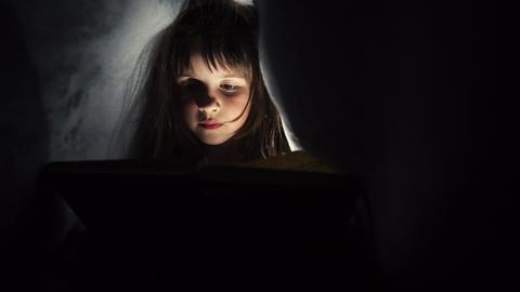 Girl reading book under blanket ビデオ