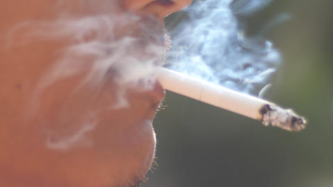 Close-up Of A Man Lighting A Cigarette And Inhaling stock footage