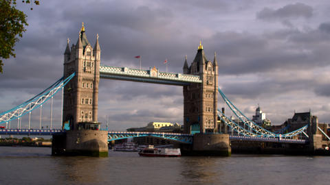 Ship passes under Tower bridge with dark clouds in distance in London, England Footage