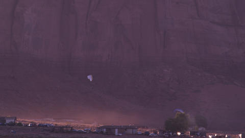 Panning shot of powered paragliders flying over town in the evening Footage