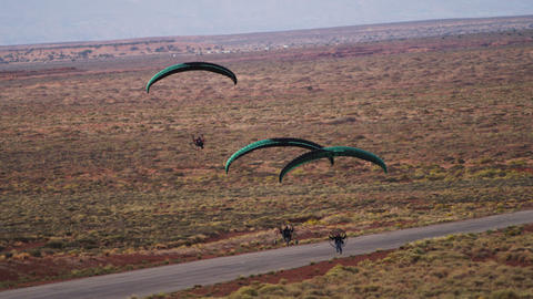 Panning shot of three powered paragliders coming in for landing Footage