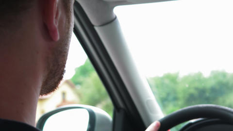 Young bearded man driving car on road. Shallow depth of field. 4k UHD video Live Action