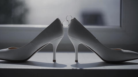 Two wedding rings rolling together near bride's wedding shoes Footage