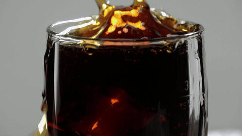 A splash of ice cold Cola - Ice cubes fall in a glass of soda Live Action
