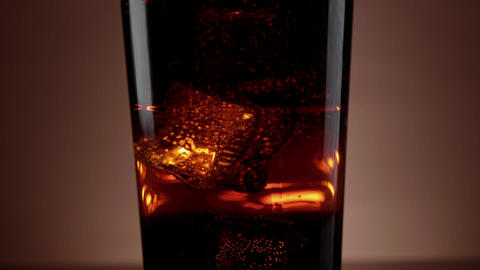 Ice cold Cola with ice cubes in soda - slow motion shot Live Action