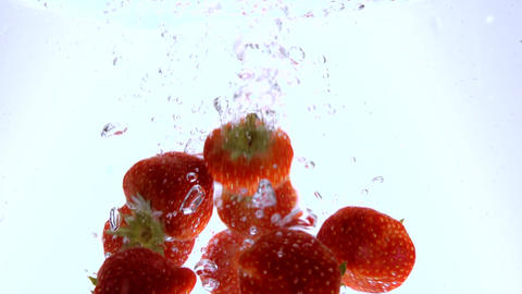 Slow motion shot of strawberries falling into water - very refreshing Footage