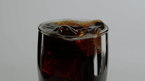 Ice cubes fall in a glass of Cola in slow motion - refreshing soda Live Action