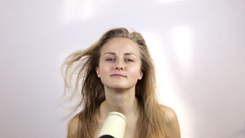 Woman after taking a shower dries wet hair Live Action