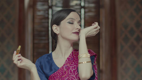 Hindu woman opening bottle and applying perfume Footage