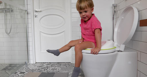 Cute toddler boy sitting on toilet in bathroom Archivo