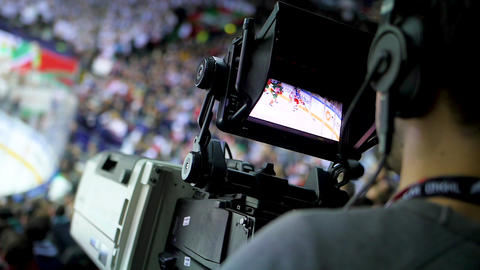close backside view cameraman films hockey game on stadium Footage