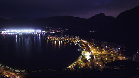 Pan of metropolis and lagoon in Rio de Janeiro, Brazil at night Footage
