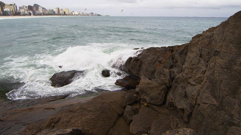 Static shot from rock of waves crashing with city in distance Footage