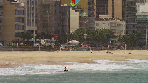 Panning shot of parasailing surfer catching a wave in Rio Footage