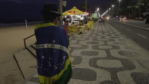 Shot following man with top hat wrapped in Brazilian flag Footage