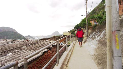 Panning shot of shanties and a walking man at a favela in Rio de Janeiro, Brazil Footage