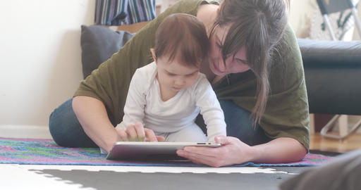 Young Mother using Tablet with her Baby Daughter Footage