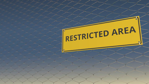RESTRICTED AREA text on the yellow plate on a mesh wire fence against blue sky Live Action
