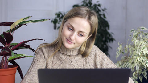 Young woman in home clothes sits behind a laptop and quite shows thumbs up Live Action