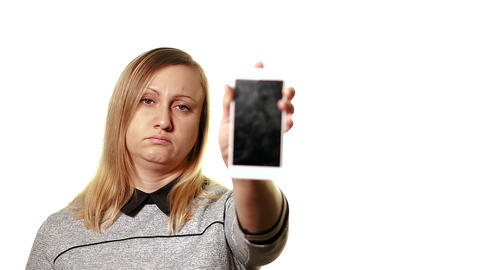 The concept of a broken gadget. A frustrated and tired middle-aged woman shows a Live Action